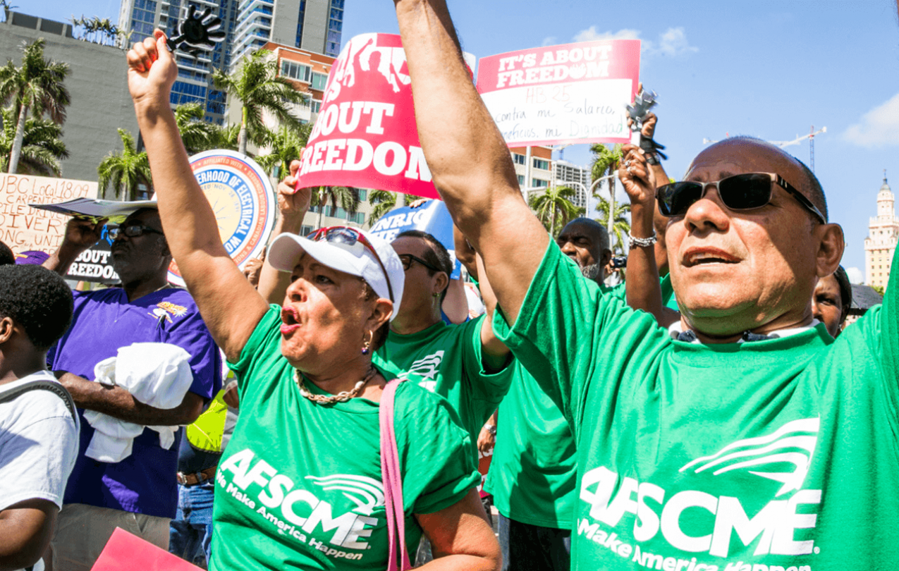 """AFSCME members at Florida rally holding signs reading """"It's about freedom."""""""